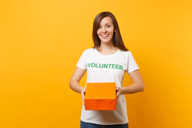 Portrait of smiling woman in white t-shirt with written inscription green title volunteer hold orange cardboard box isolated on yellow background. voluntary free assistance help, charity grace concept