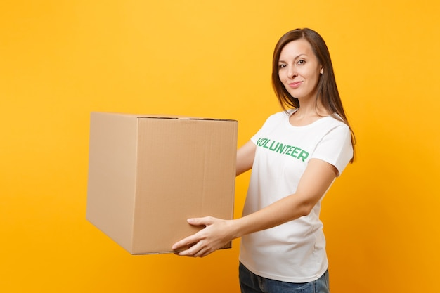 Portrait of smiling woman in white t-shirt with written inscription green title volunteer with big cardboard box isolated on yellow background. voluntary free assistance help, charity grace concept.