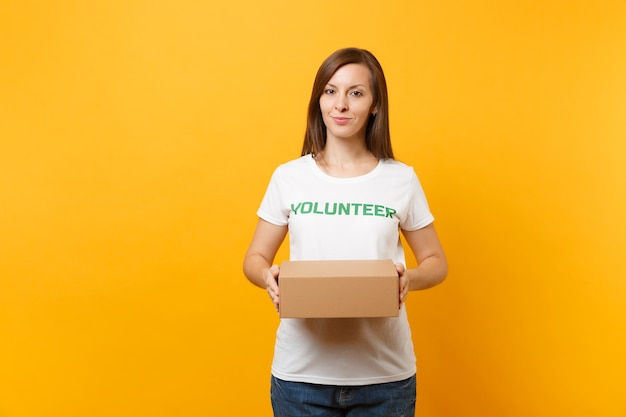 Portrait of smiling woman in white t-shirt with written inscription green title volunteer with blank cardboard box isolated on yellow background. voluntary free assistance help, charity grace concept.