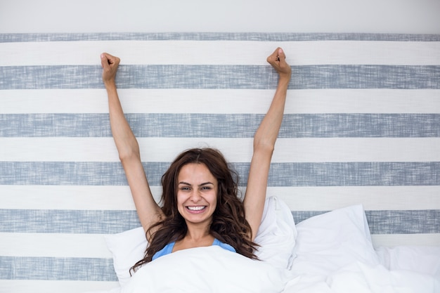 Portrait of smiling woman with arms raised