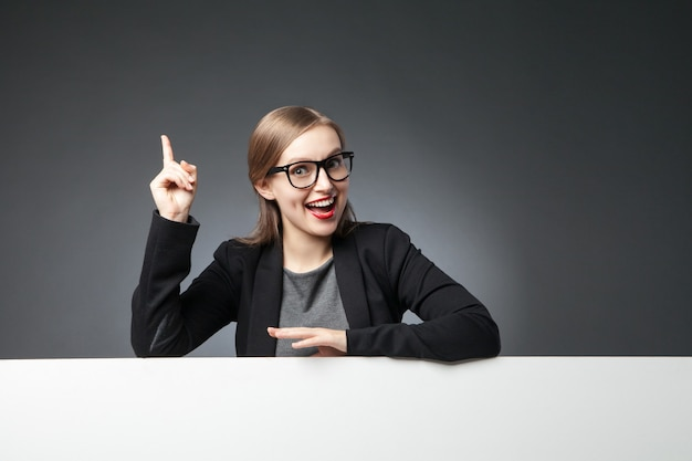 Portrait of smiling woman with index finger up looking at camera