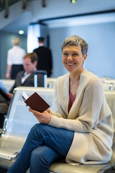 Portrait of smiling woman with passport sitting in waiting area