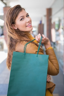 Portrait of smiling woman with shopping bag looking at camera