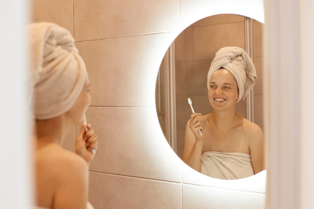 Portrait of smiling young adult woman with bare shoulders brushing her teeth, posing in bathroom after taking shower, standing with white towel on her hair.