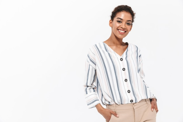 Portrait of a smiling young african businesswoman standing isolated over white wall, posing