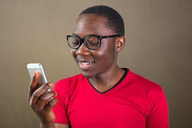 Portrait of a smiling young african man using smartphone