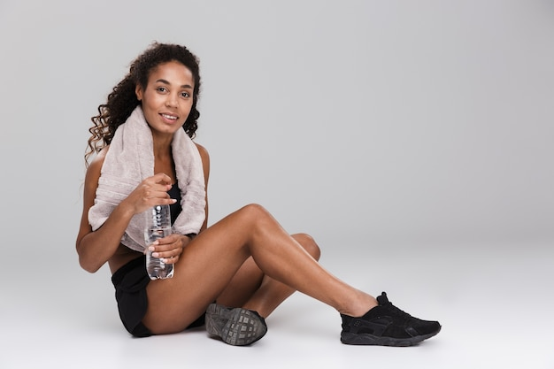Portrait of a smiling young african sportswoman resting after training isolated over grey wall, drinking water