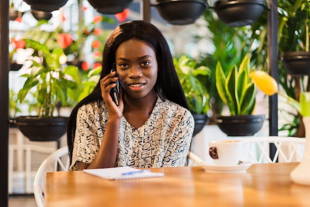 Portrait of smiling young african woman sitting at cafe making phone call