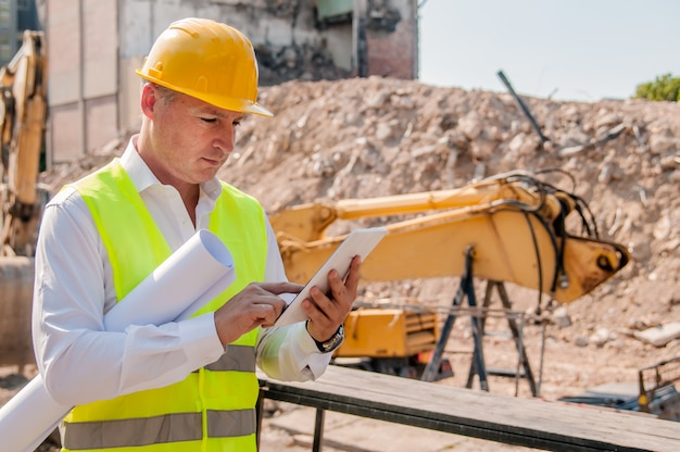 Portrait of smiling young architect or handsome engineer holding tablet and rolled up blueprints with building construction background.