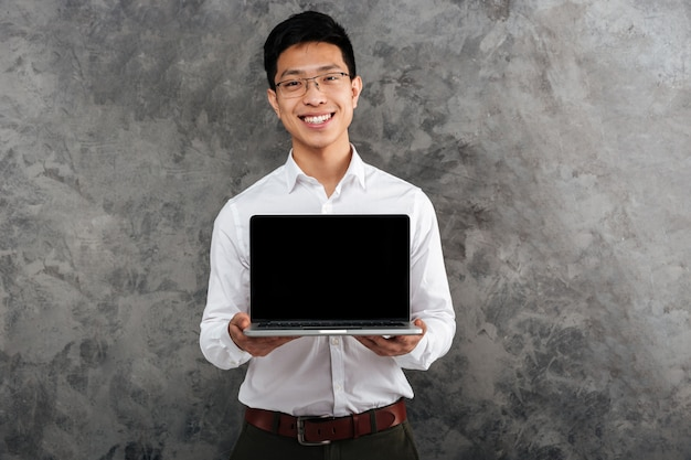 Portrait of a smiling young asian man dressed in shirt