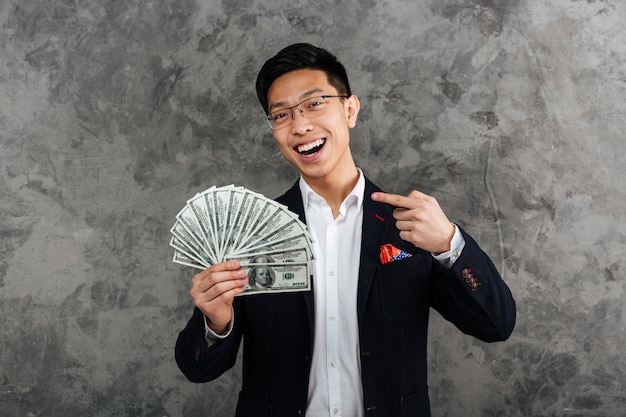 Portrait of a smiling young asian man dressed in suit