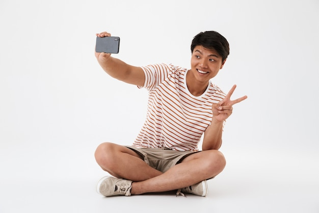 Portrait of a smiling young asian man taking a selfie