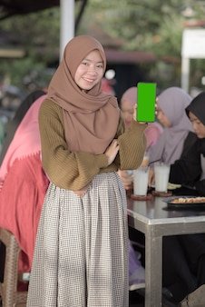 Portrait of smiling young asian teenager girl showing blank green phone screen.