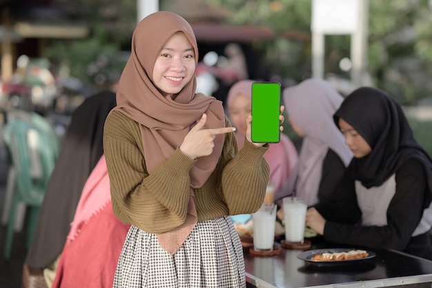 Portrait of smiling young asian teenager girl showing and pointing blank green phone screen.