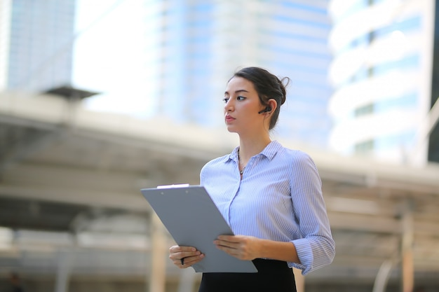 Portrait of smiling young beautiful business woman hold folder standing at outside.