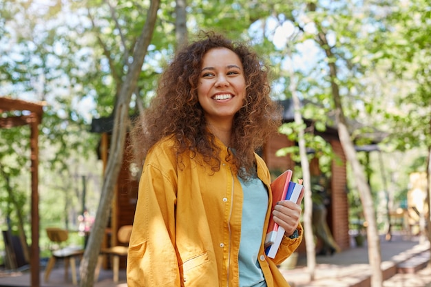 Portrait of smiling young beautiful dark skinned curly student girl on a cafe terrace, holding textbooks, wearing in yellow coat, enjoys the day.