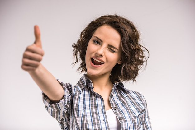 Portrait of smiling young beauty woman showing thumb up.