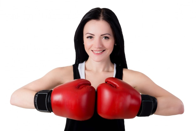 Portrait of a smiling young brunette woman with red boxing gloves.