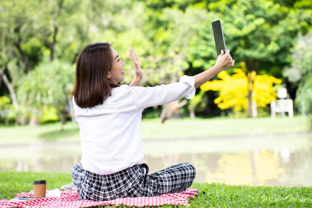 Portrait of a smiling young business woman using tablet for video call to her friend in the park with relax after working