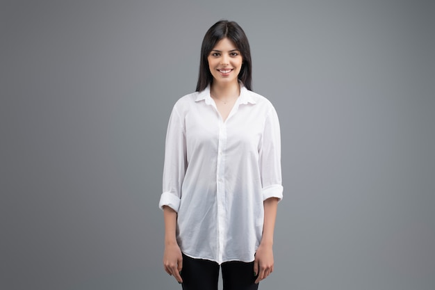 Portrait of a smiling young business woman in white shirt isolated over grey