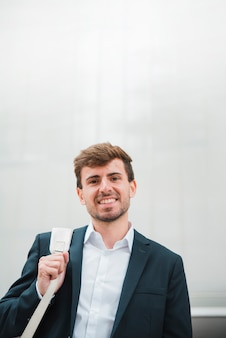 Portrait of a smiling young businessman against grey wall