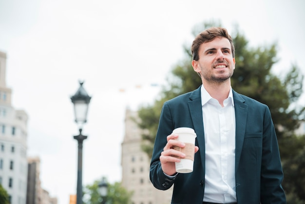Portrait of a smiling young businessman holding takeaway coffee cup in hand