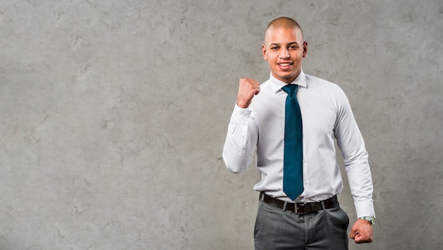 Portrait of a smiling young businessman standing against grey wall clenching his fist