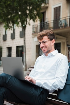 Portrait of a smiling young businessman using laptop