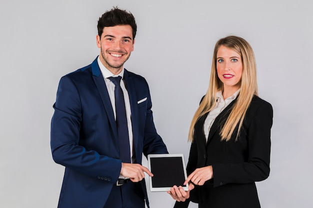 Portrait of a smiling young businesswoman and businessman pointing digital tablet against grey backdrop