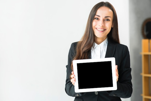Portrait of a smiling young businesswoman showing touch screen digital tablet