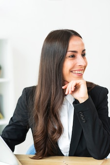 Portrait of smiling young businesswoman sitting at office desk