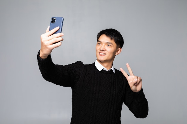 Portrait of a smiling young chinese man taking a selfie with mobile phone while isolated over white wall