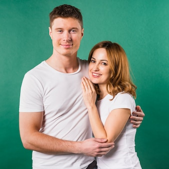 Portrait of smiling young couple against green background