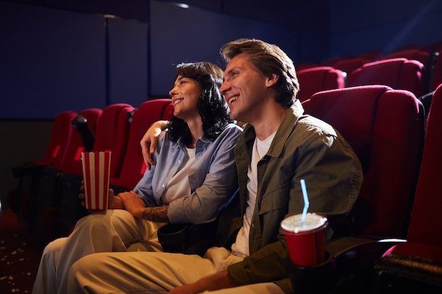 Portrait of smiling young couple in cinema watching movie together and embracing while enjoying romantic date, copy space
