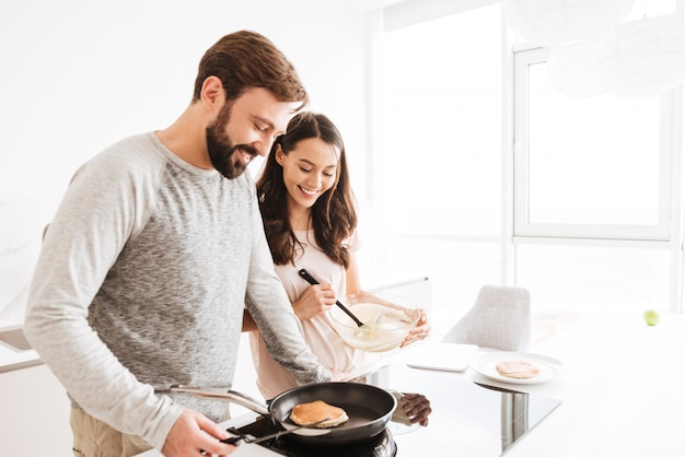 Portrait of a smiling young couple cooking pancakes