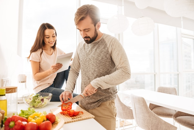 Portrait of a smiling young couple cooking