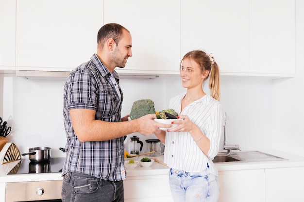 Portrait of a smiling young couple holding bowl of raw vegetables in hands
