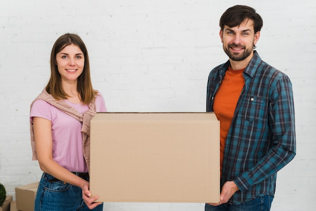 Portrait of a smiling young couple holding cardboard box in hand looking to camera