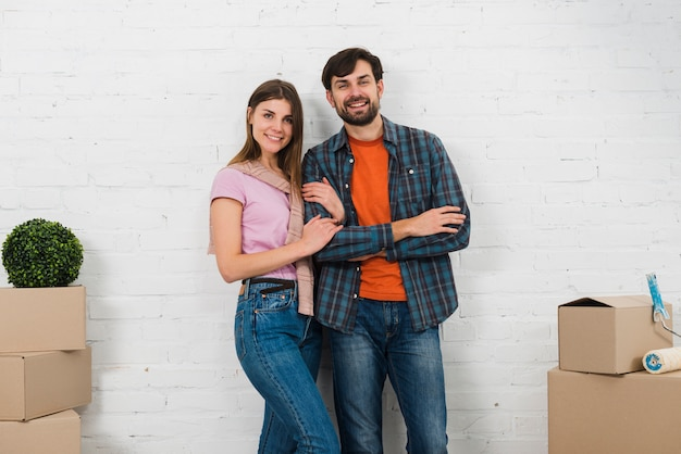 Portrait of smiling young couple standing in front of white wall looking to camera