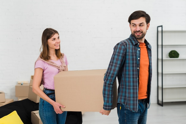 Portrait of a smiling young couple together holding moving cardboard box