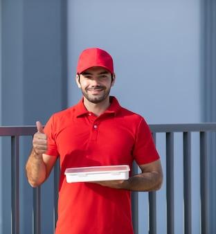 Портрет улыбающийся молодой курьер в красной форме, держащий коробку перед домом.