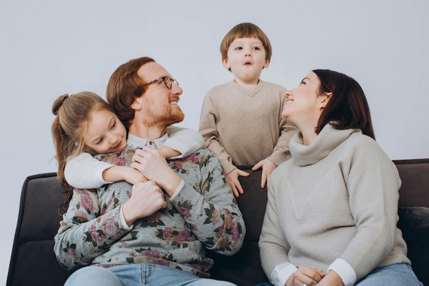 Portrait of smiling young family with little preschooler kids sit on couch in living room.
