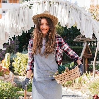 Ritratto di un giovane giardiniere femminile sorridente che tiene strumento e canestro di giardinaggio