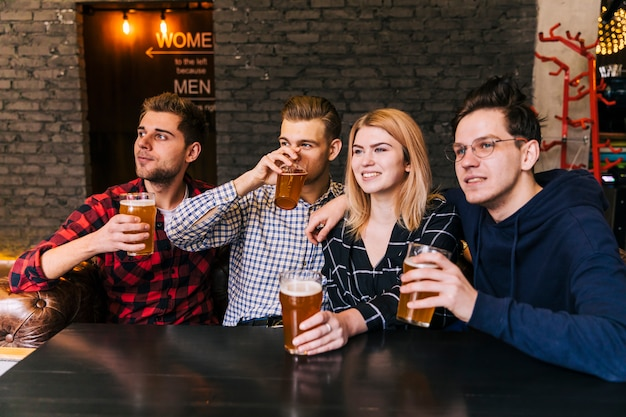 Portrait of a smiling young friends enjoying the beer