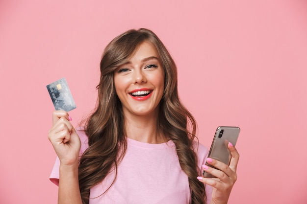 Portrait of a smiling young girl showing credit card