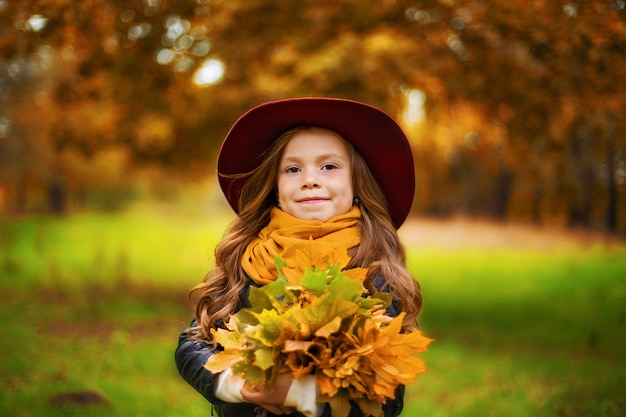 Portrait of a smiling young girl who is holding in her hand a bouquet of autumn maple leaves.