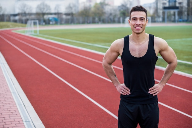 Portrait of a smiling young male athlete standing on race track