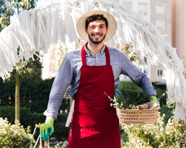 Ritratto di un giovane giardiniere maschio sorridente che tiene strumento e canestro di giardinaggio che esaminano macchina fotografica