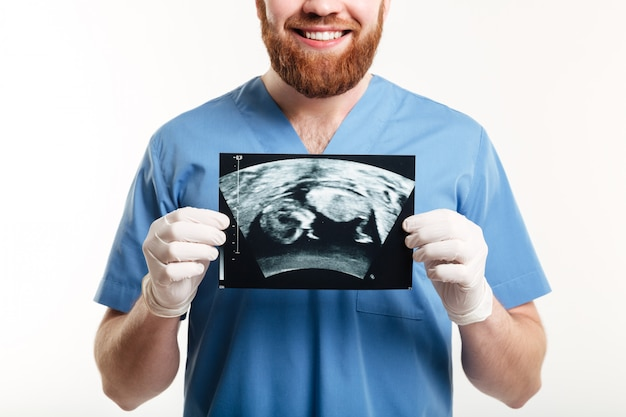 Portrait of a smiling young male medical doctor showing radiograph