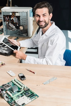 Portrait of a smiling young male technician holding digital tablet